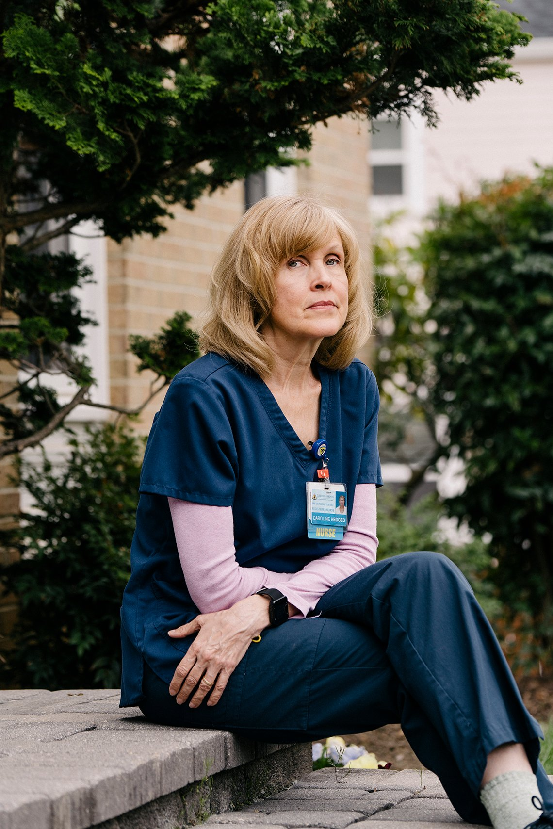 a middle aged nurse sits on the front steps of her building looking pensive