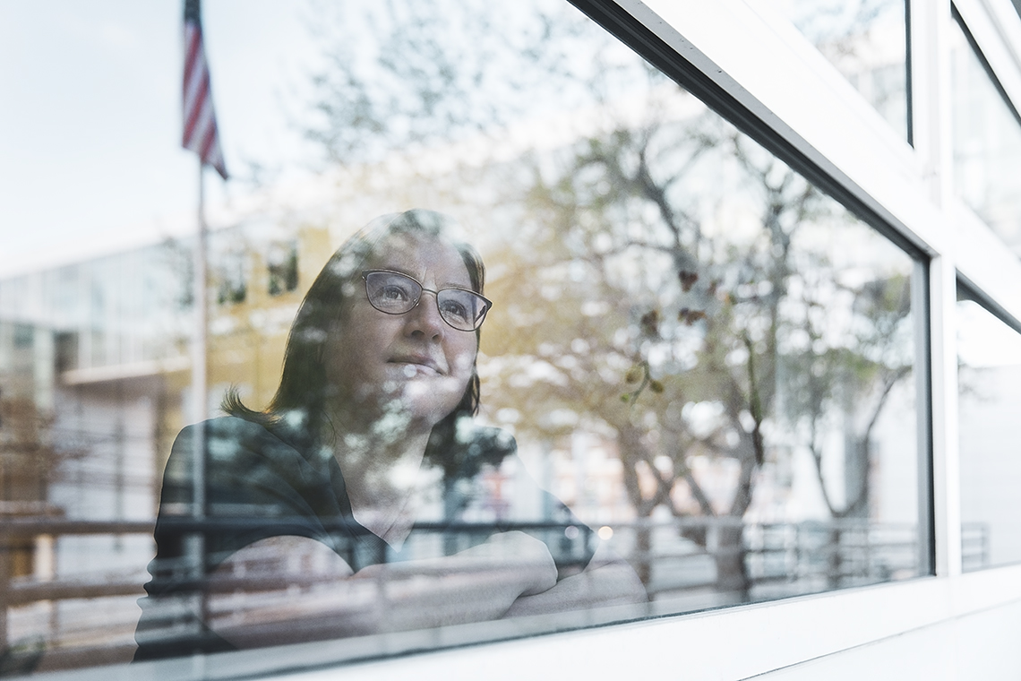 a nurse looks at a window shot form outside partially obscured by the trees and an american flag on a pole reflected in the window