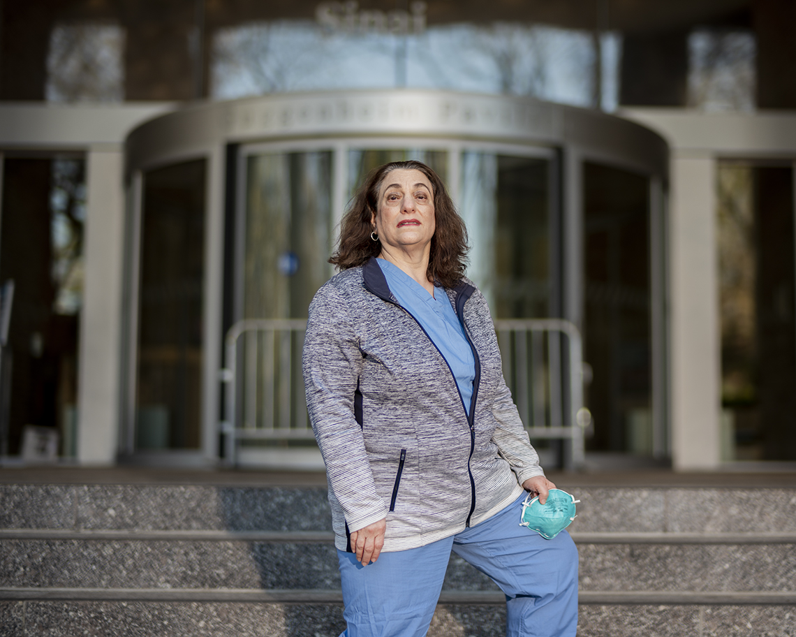 a nurse stands looking exhausted on the front steps of a hospital holding her face mask on one hand