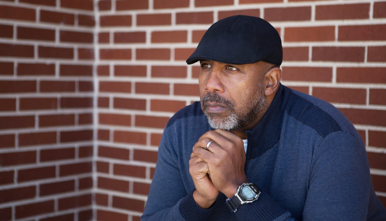 Un hombre, con sus manos juntas en la barbilla, luce preocupado
