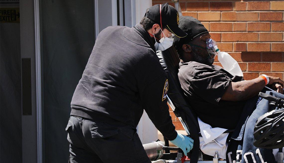 Un paramédico transporta a un hombre afroamericano en una camilla