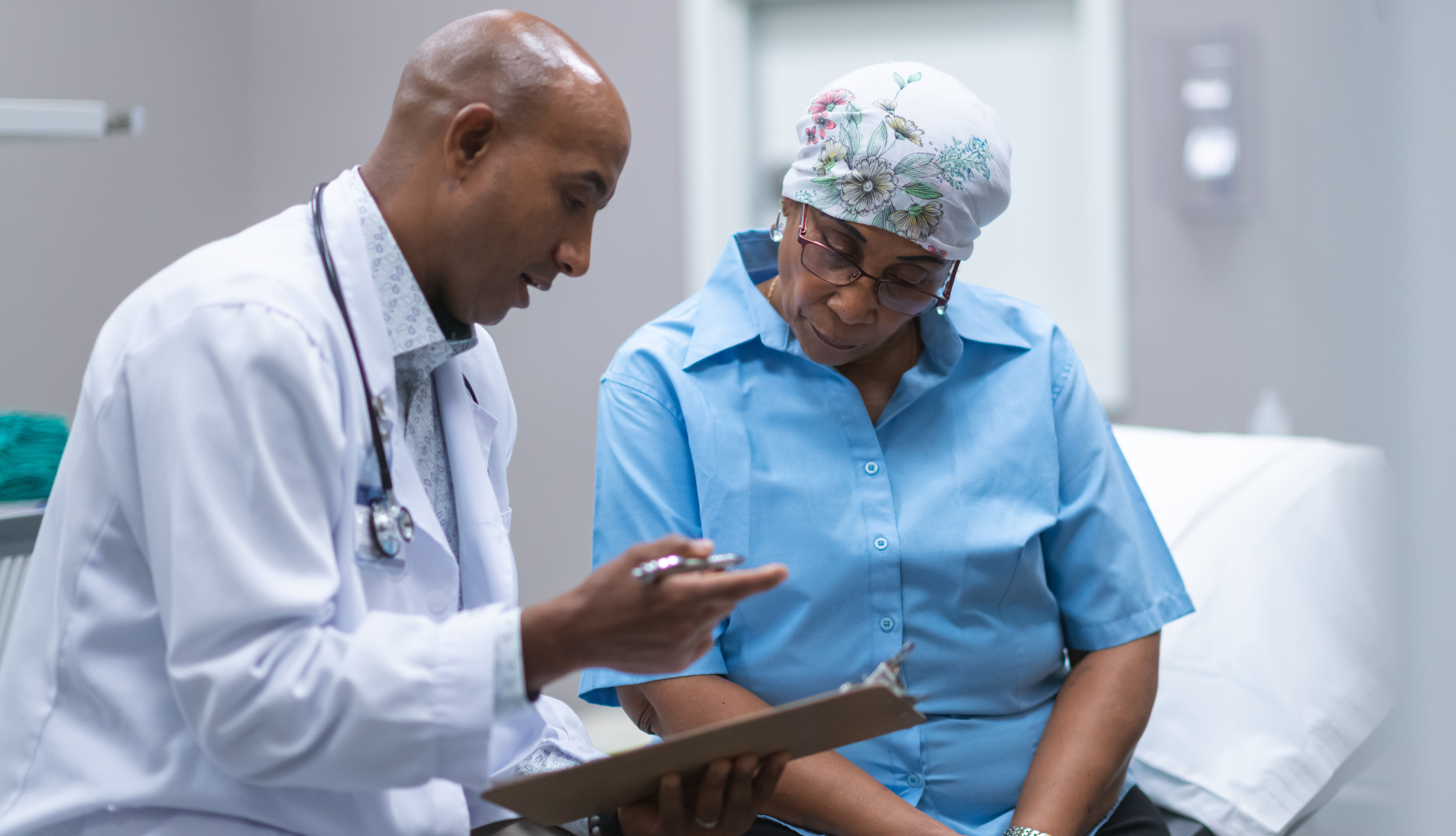 an african american woman with cancer talking to her doctor, who is also african american