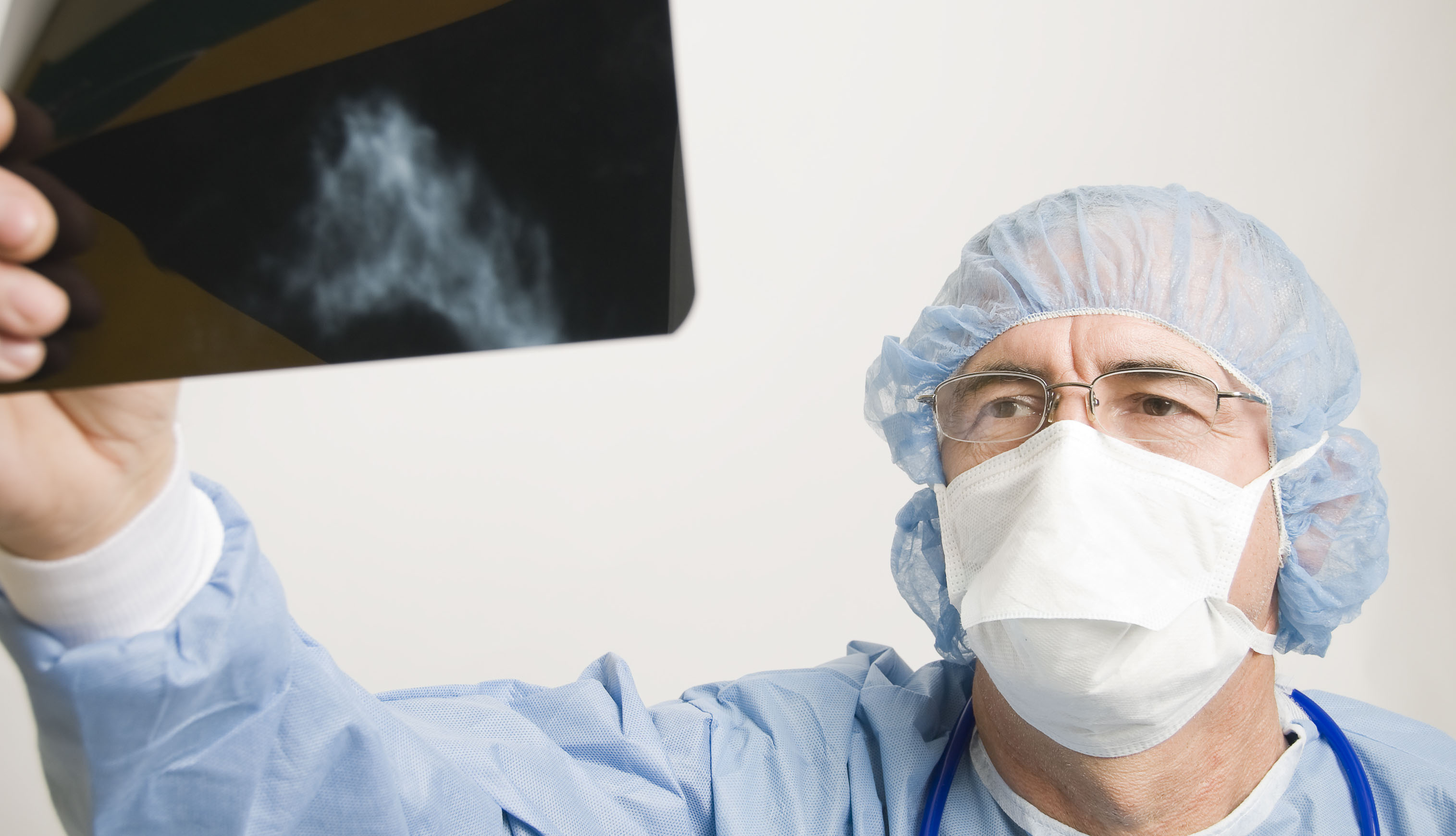 doctor wearing protective gear looking at an x-ray