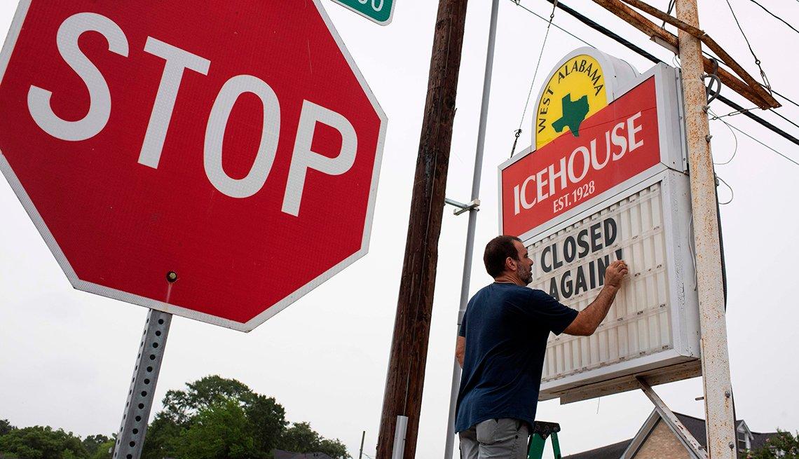Un hombre coloca un letrero que dice cerrado otra vez