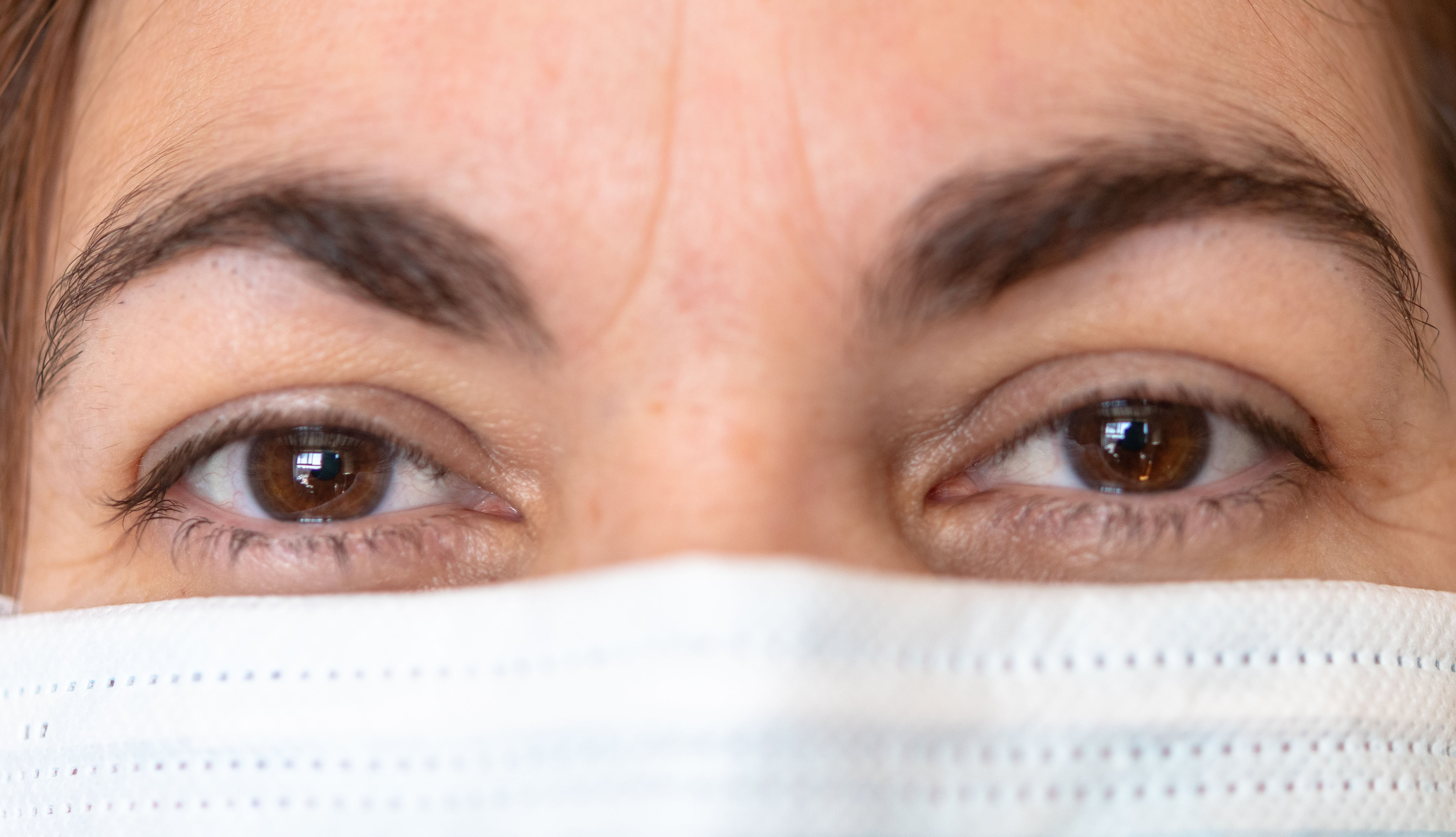 close up of a woman's eyes and nose and she is wearing a face mask