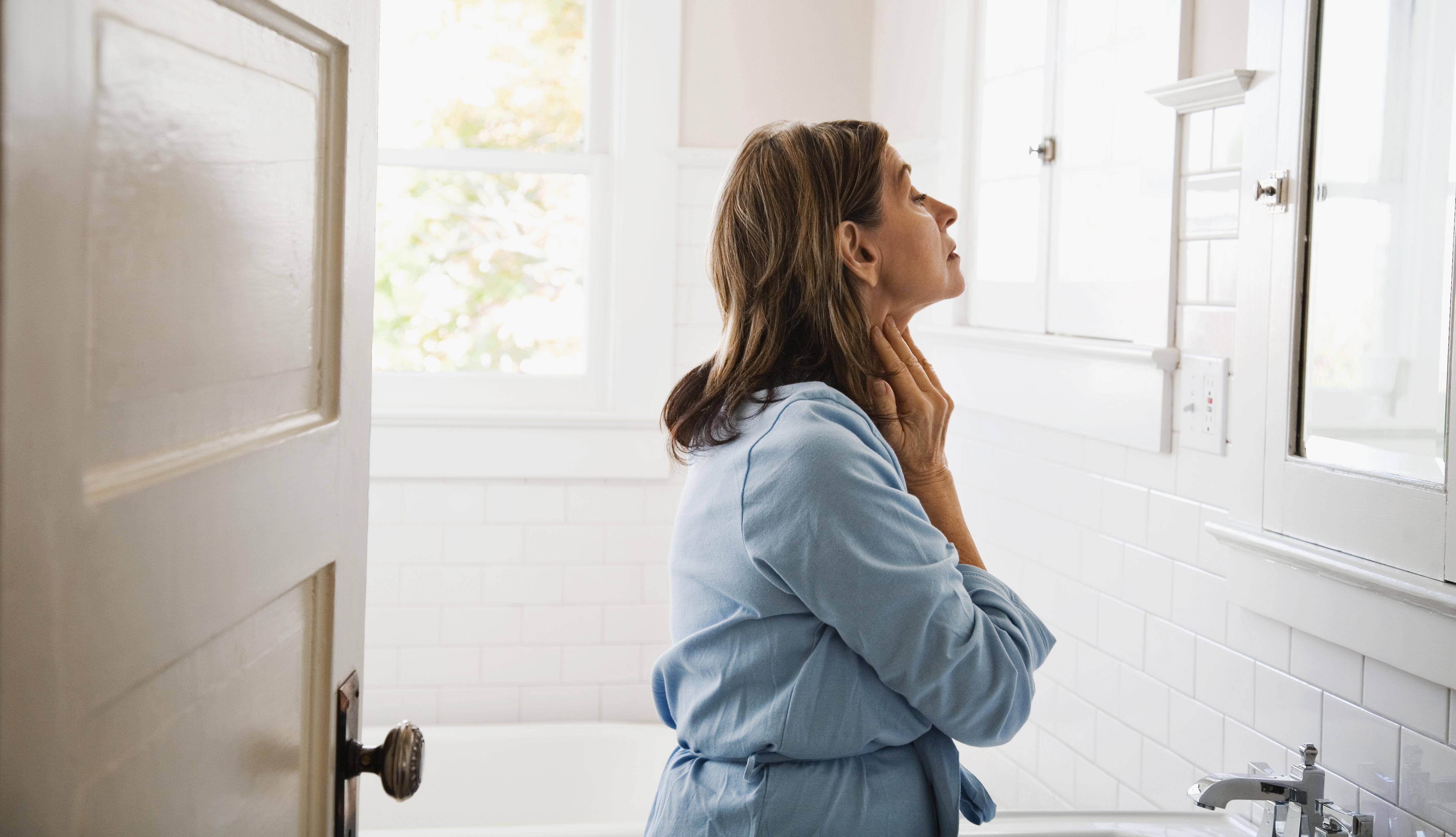 Una mujer se mira e inspecciona su apariencia frente a un espejo