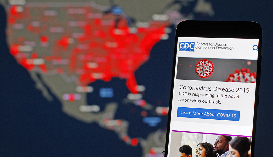 A Centers for Disease Control and Prevention (CDC) mobile web screen on the topic of the Coronavirus Disease 2019 is  displayed over an illustrated map of the United States that tracks the virus