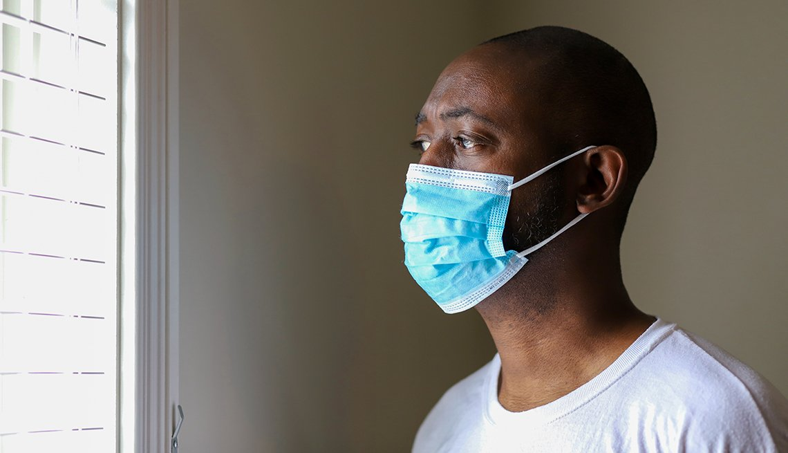man looking out a window wearing a medical face mask