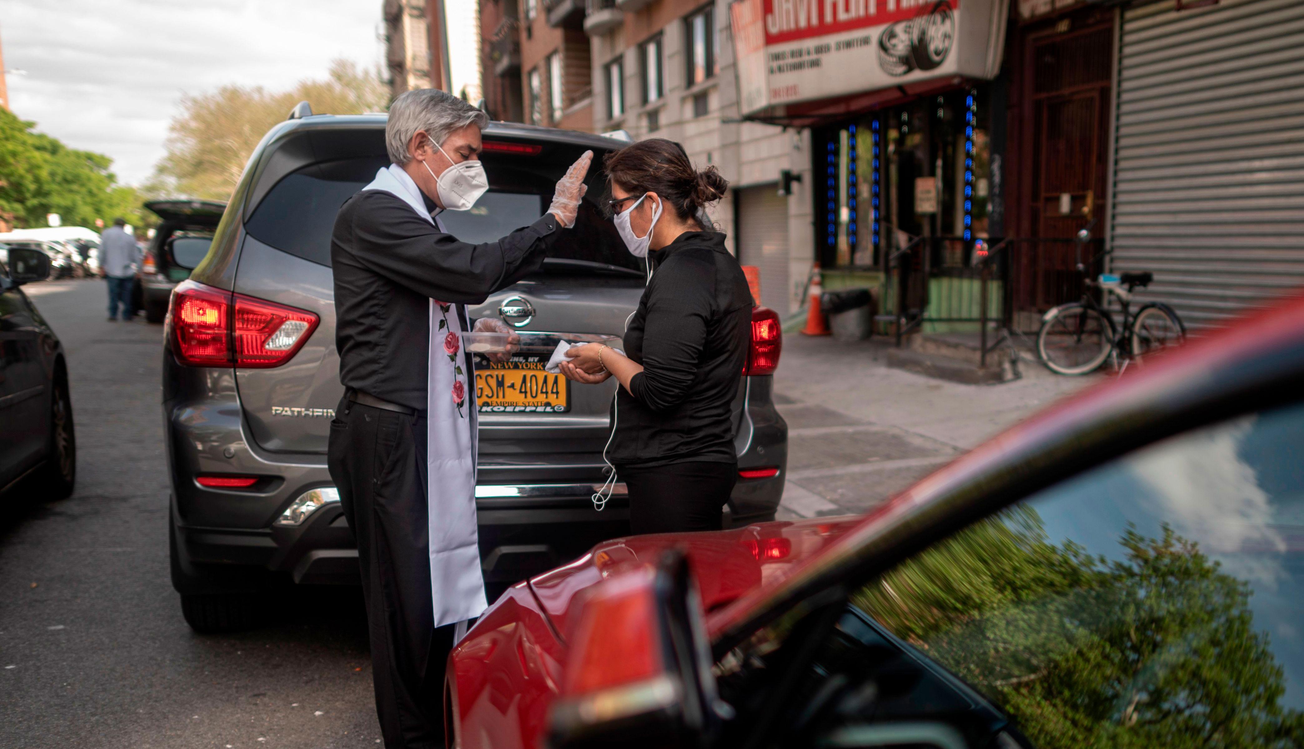 item 1 of Gallery image - Fabian Arias, un pastor luterano de la Iglesia de San Pedro en Manhattan, entrega la comunión a un miembro de la comunidad