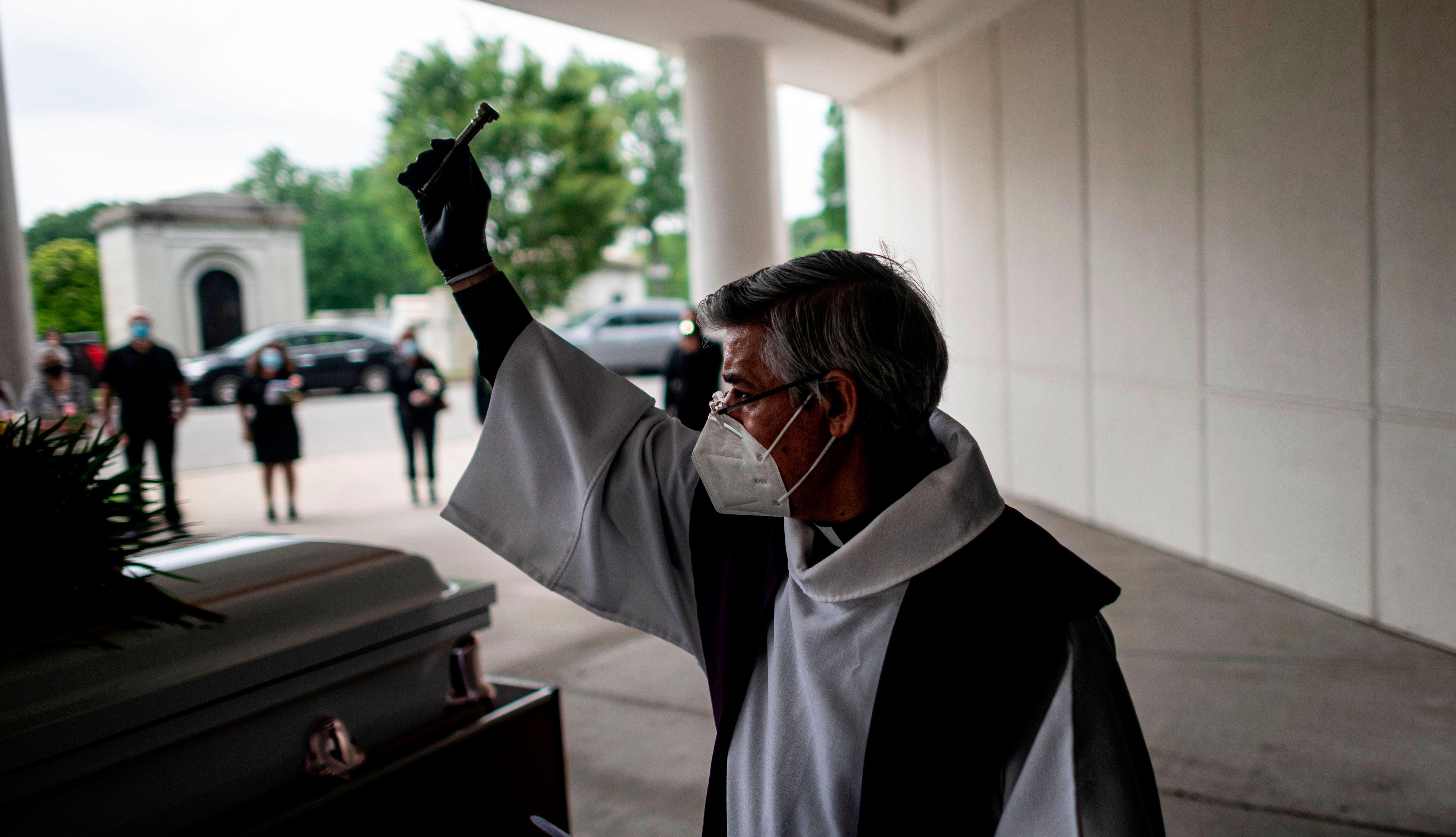 item 2 of Gallery image - Fabian Arias, un pastor luterano de la Iglesia de San Pedro en Manhattan, usa una mascarilla y guantes mientras celebra un funeral