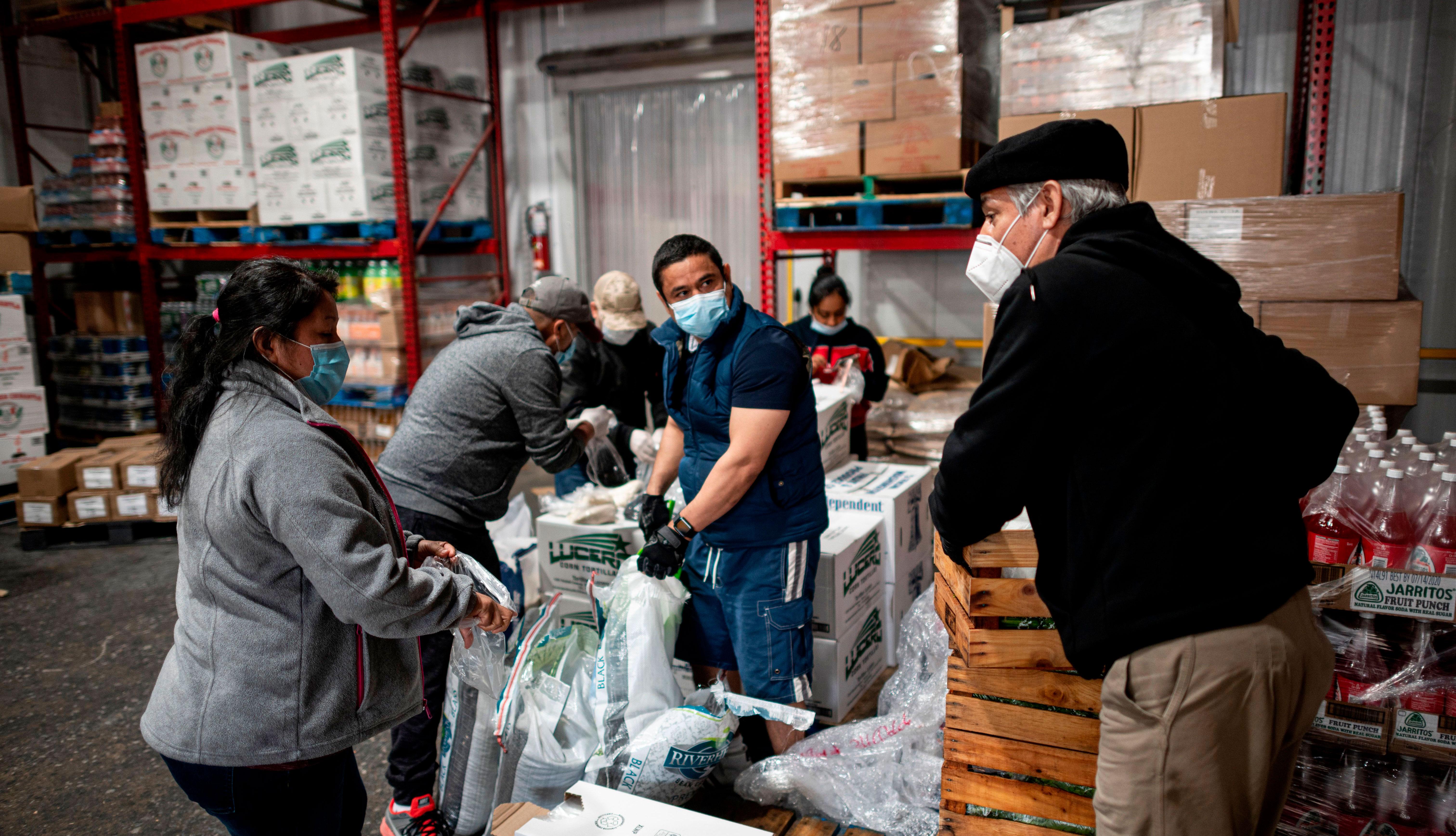 item 3 of Gallery image - El pastor luterano Fabian Arias habla con otros voluntarios mientras preparan y cargan alimentos para donar