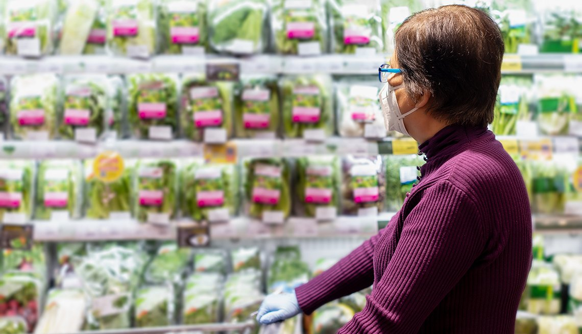 a woman wearing a face mask and gloves pushes a cart in a grocery store in an aisle of bagged salad