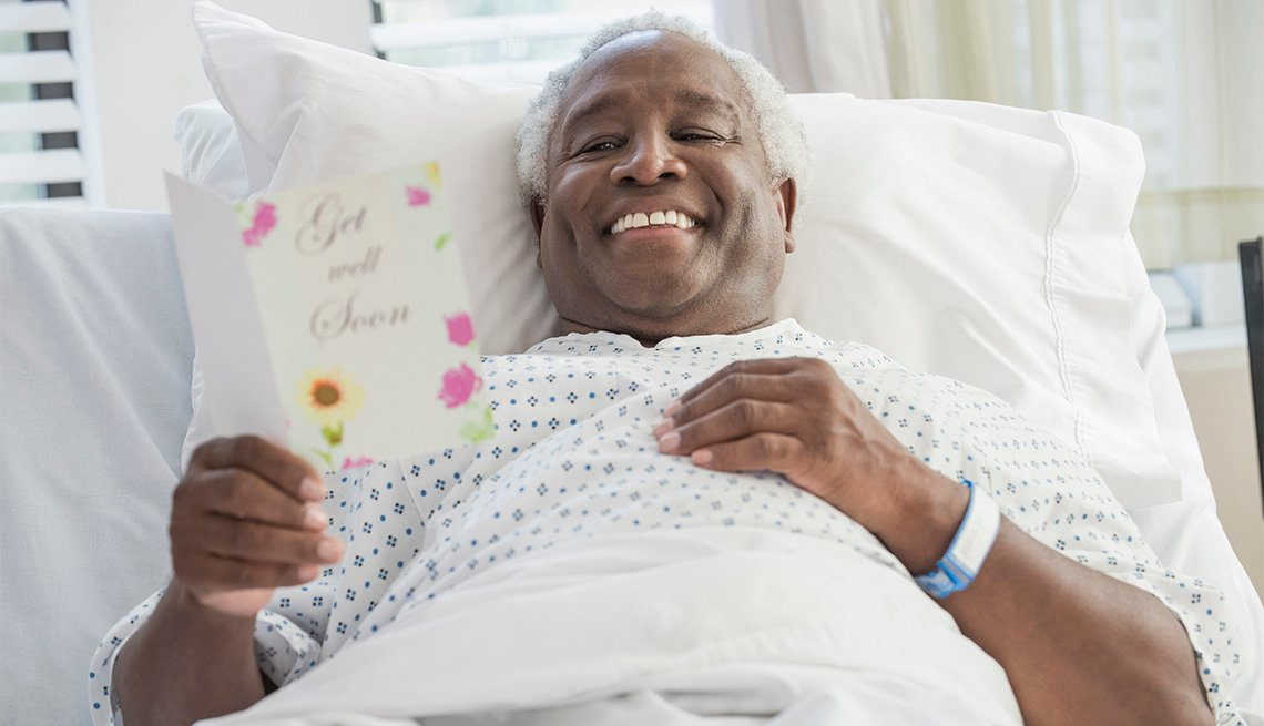 man reading get well soon card in hospital bed