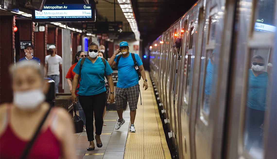 People wearing protective masks walk through the Essex Street subway station in New York