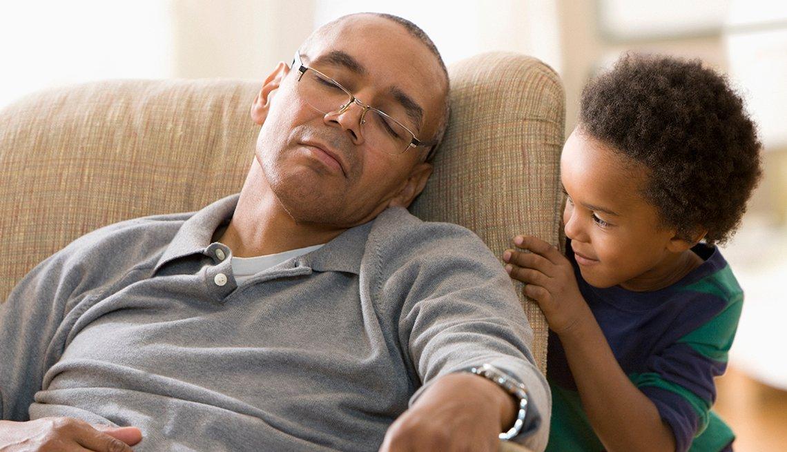 Un hombre toma una siesta mientras un niño pequeño lo espía