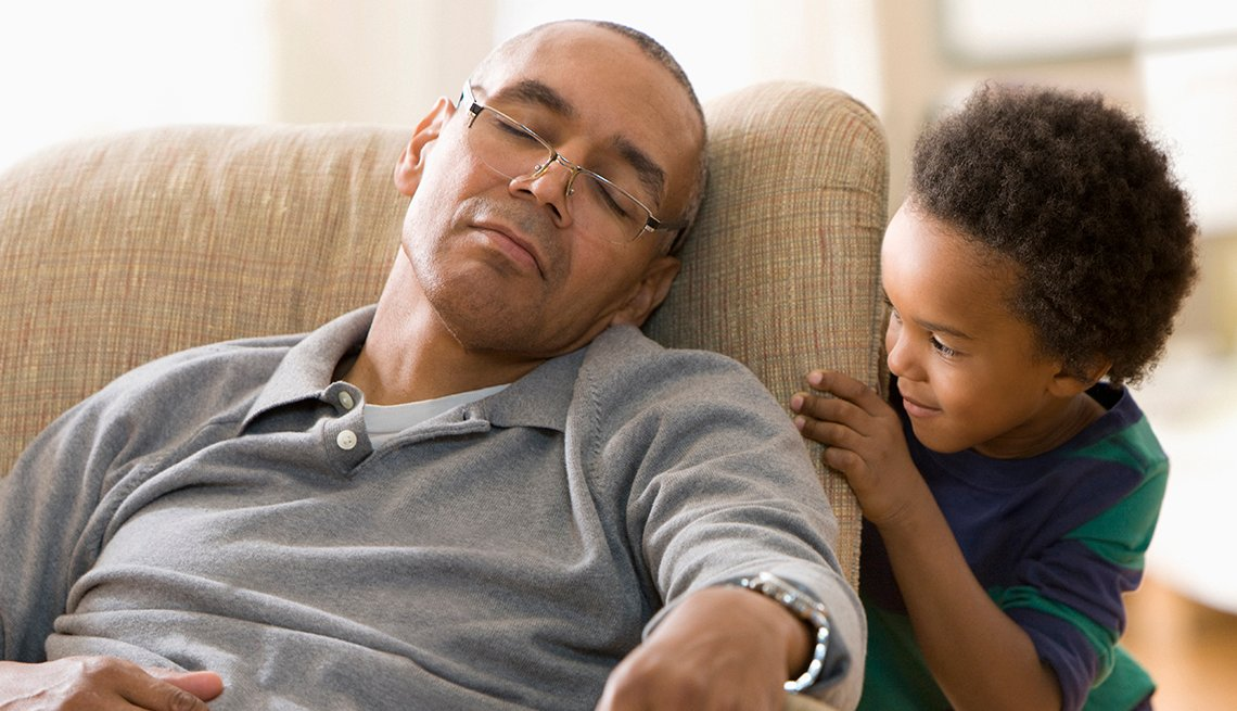 Older man sleeping in chair as a young child peeks at him