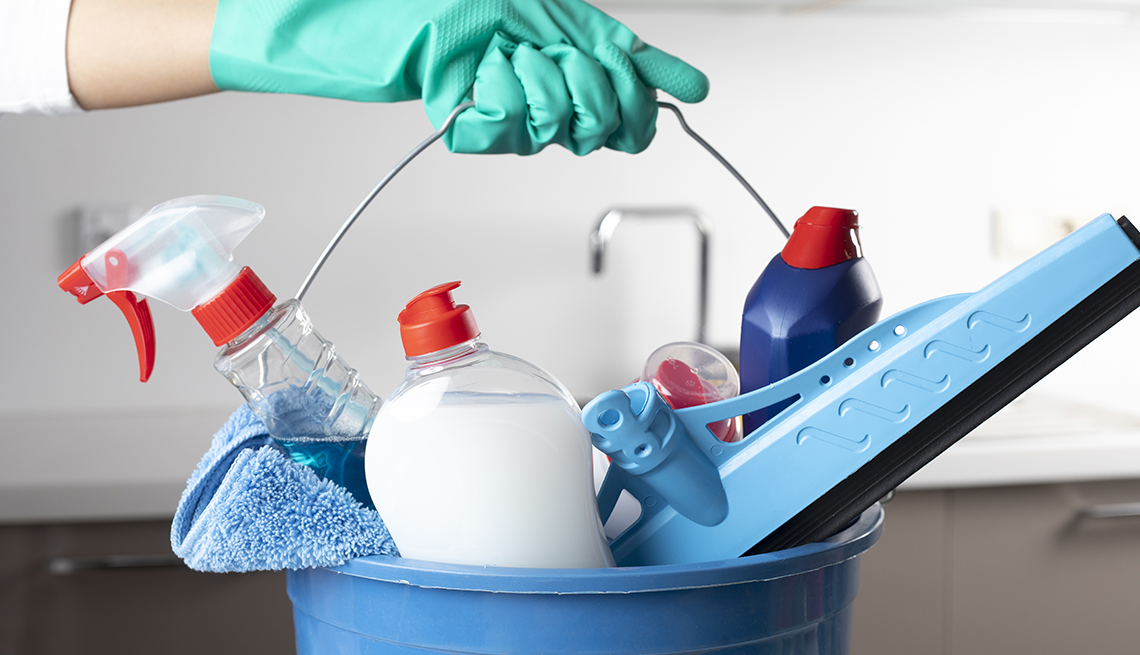 Una mano con guantes sostiene un cubo con productos de limpieza