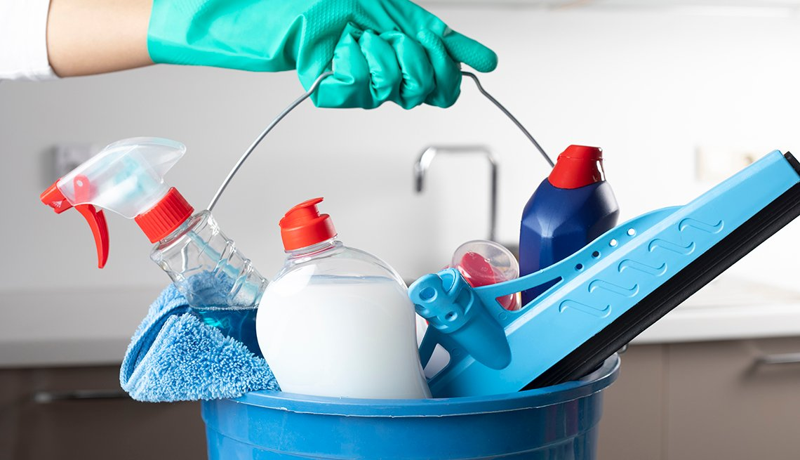 person holding bucket of cleaning products with gloved hand
