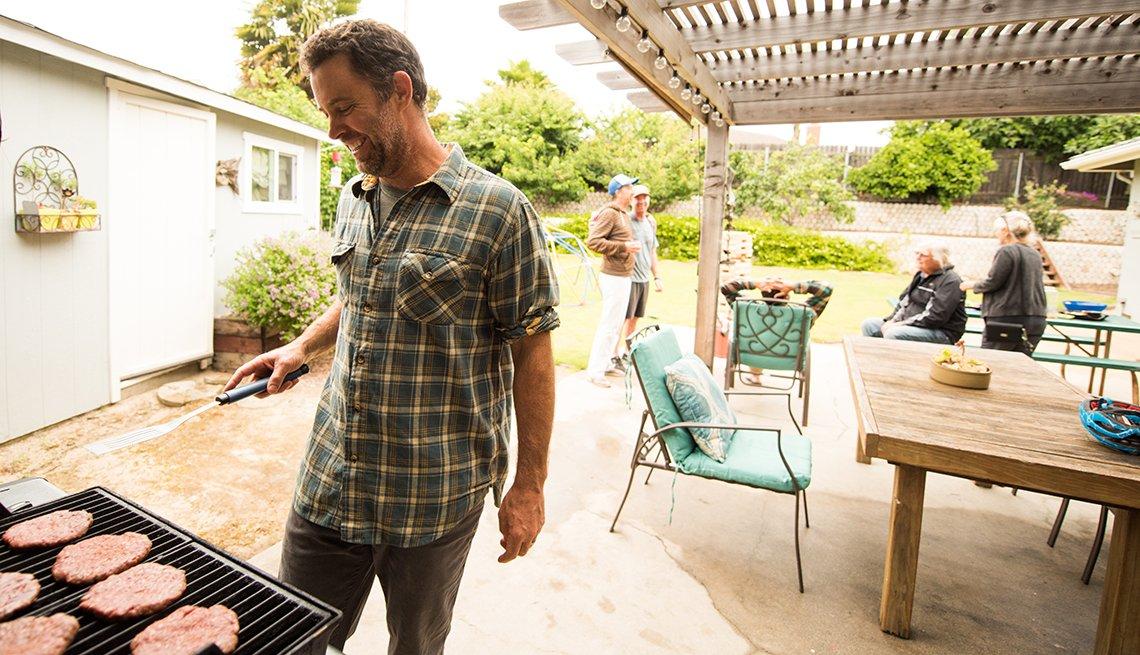 Un hombre hace hamburguesas a la barbacoa en su patio
