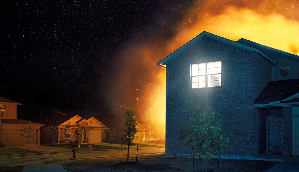 a house on fire at night time as seen from outside