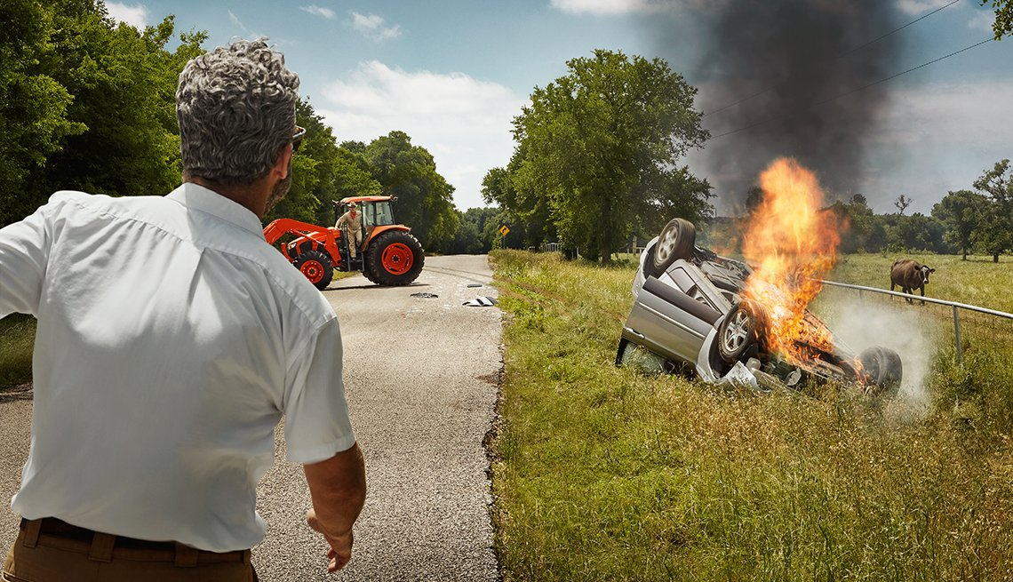 back of man running towards the scene of a vehicle accident on a country road with a car flipped over and on fire