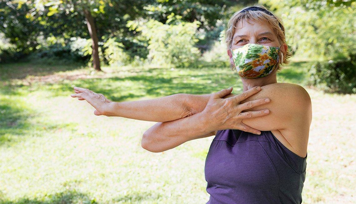 Una mujer hace ejercicio afuera en un parque mientras usa una mascarilla