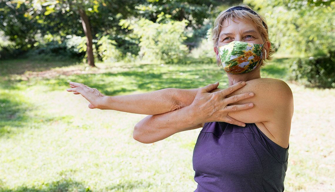 woman exercising outside at the park while wearing a mask