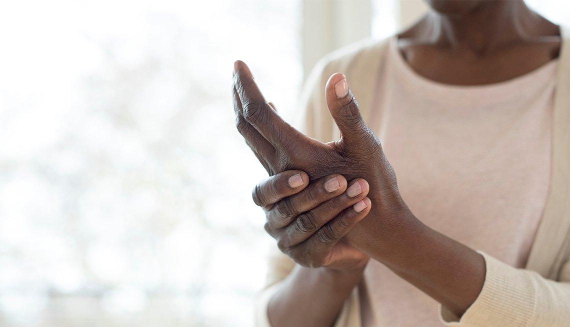 Una mujer se masajea sus manos para aliviar el dolor de la artritis