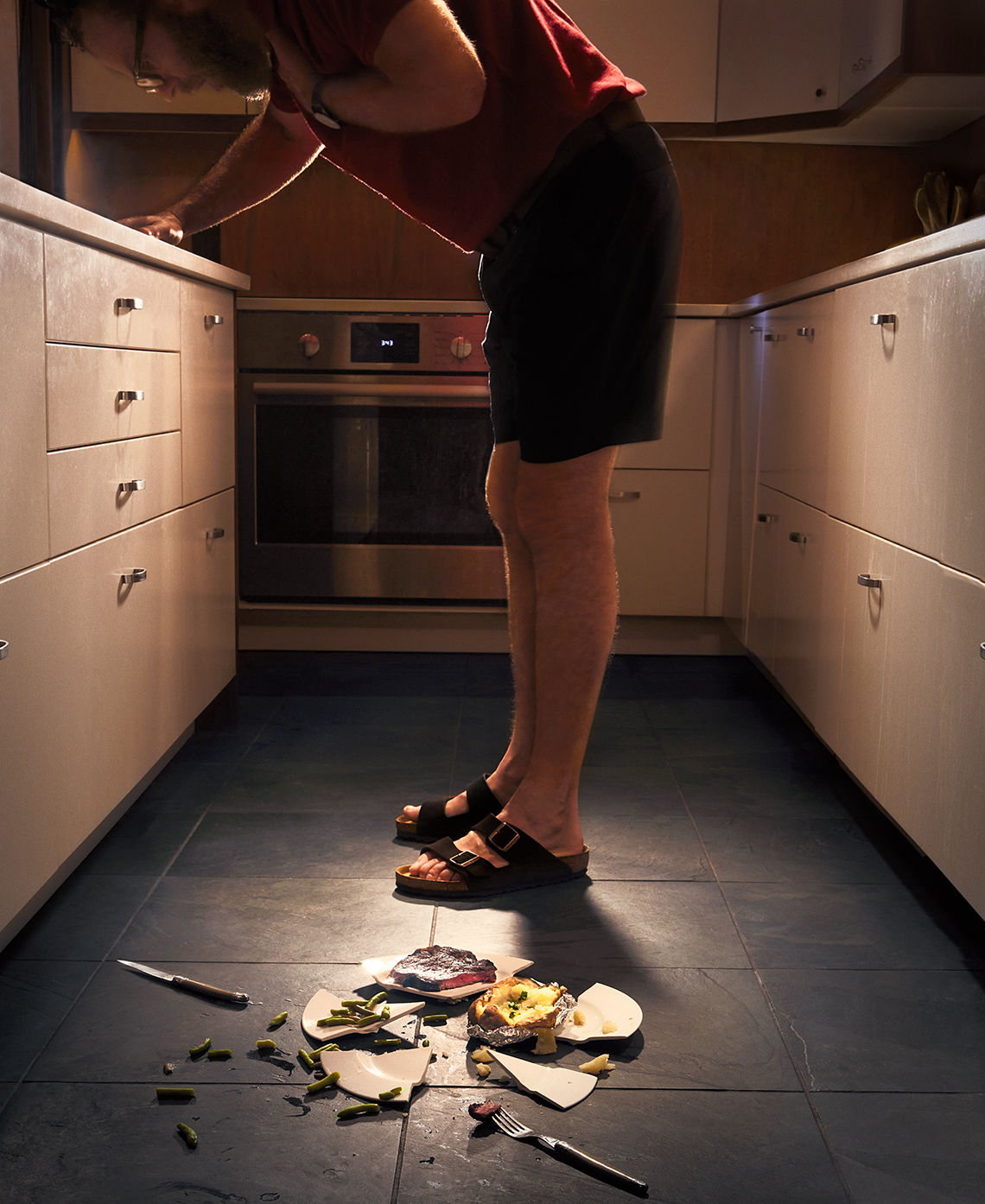 man in his kitchen bending over and choking on food, there is a broken plate of food at his feet