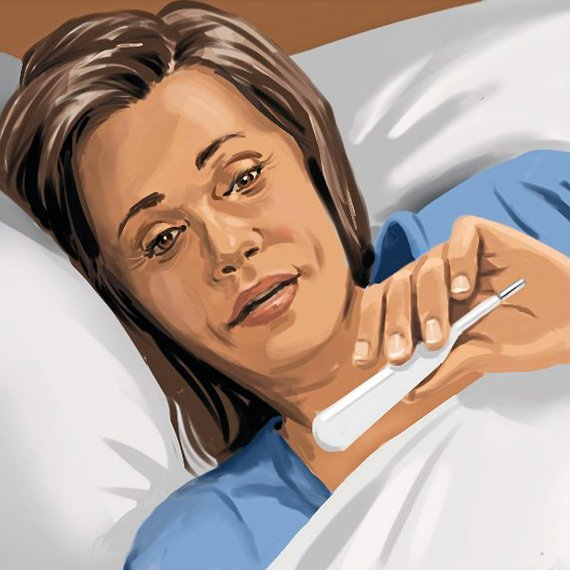 woman lying sick in bed is checking her temperature