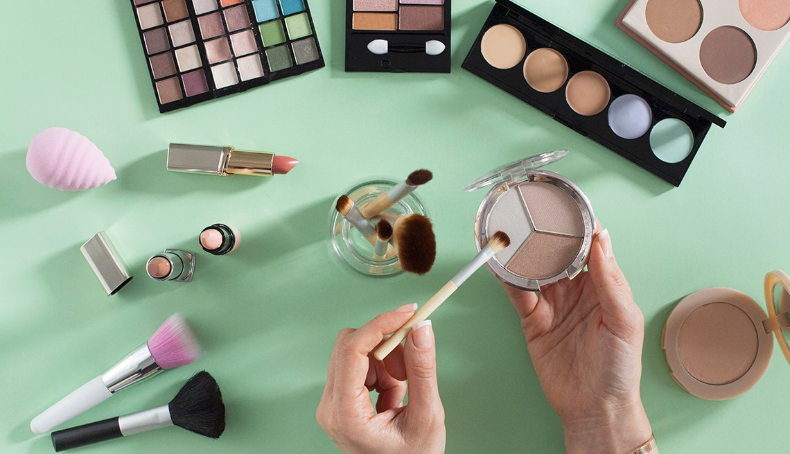 Various types of makeup on a green background. Woman's hands holding eyeshadow and a brush.