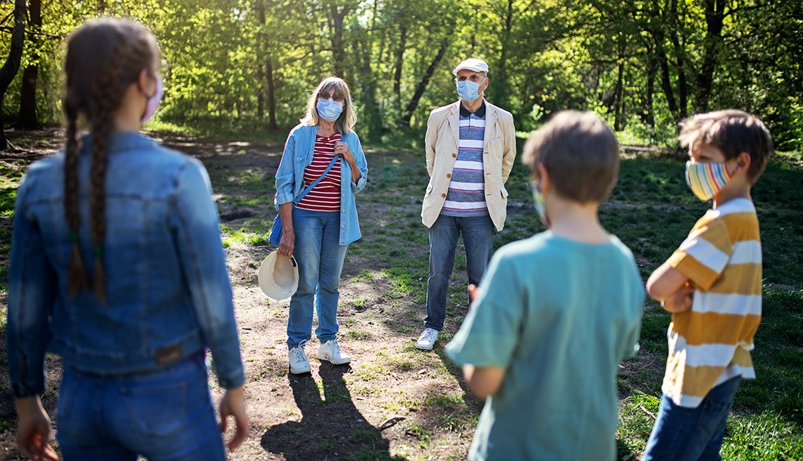 three siblings and their grandparents stand in a large circle in a park socially distanced and wearing masks