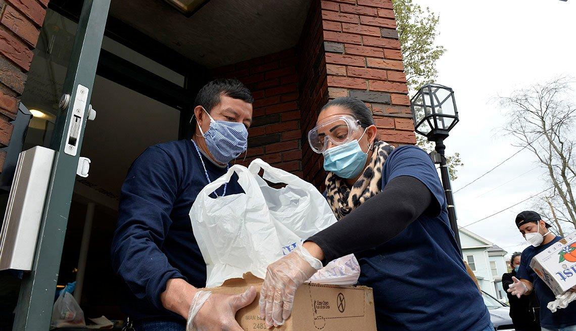 Una mujer le entrega una caja con alimentos a una mujer, ambos usan mascarillas