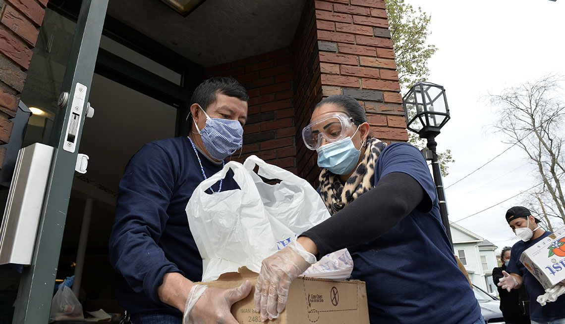 A man handing donated food to a woman to help people in the Hispanic community with coronavirus. Both are wearing face masks.