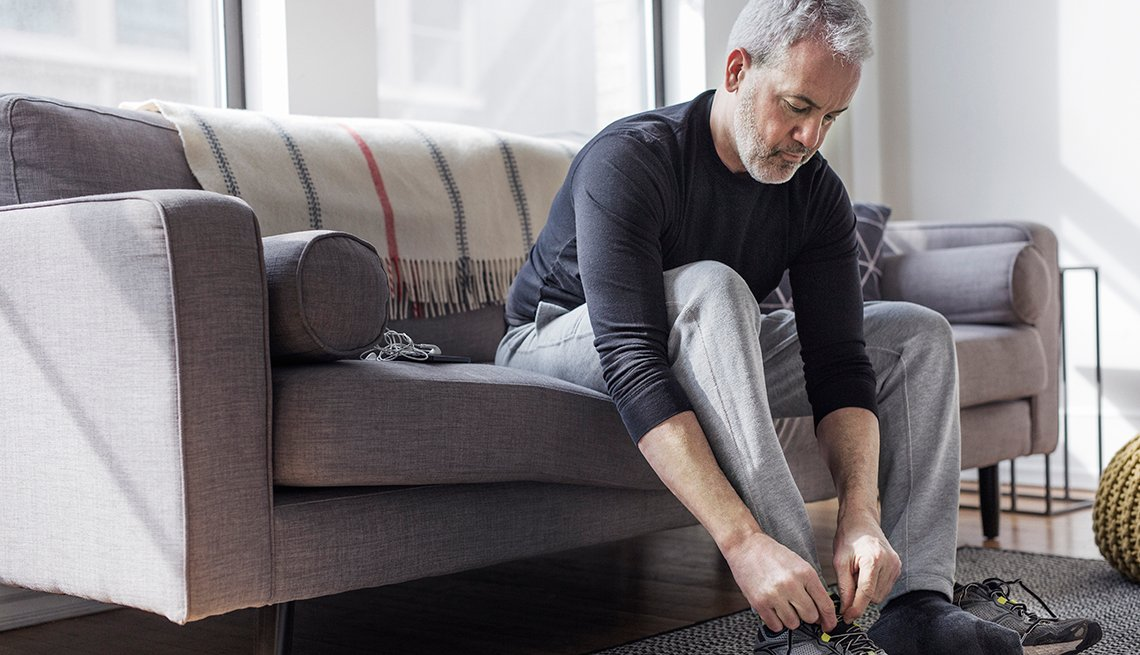 Man sits on couch and ties his sneaker