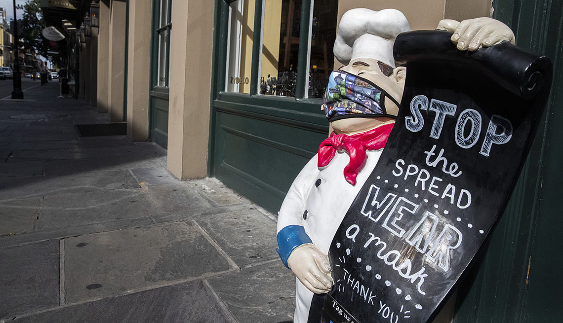 """Statue of chef in New Orleans wearing a face mask holding a sign that says """"stop the spread-wear a mask"""""""