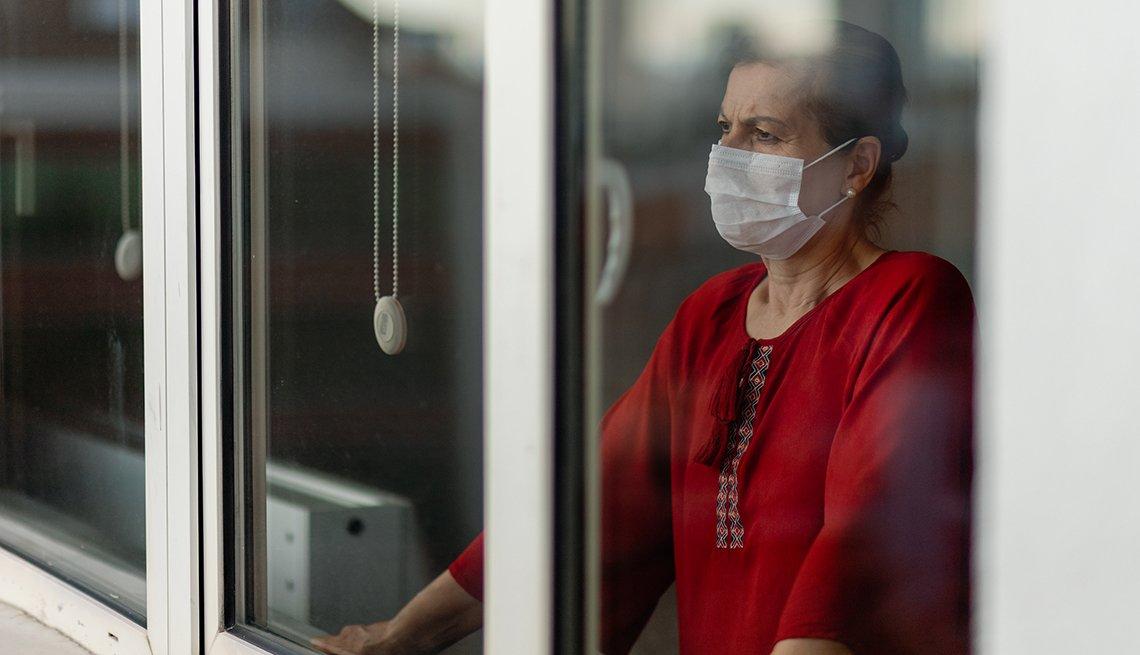 Una mujer, con mascarilla, mira a través de una ventana