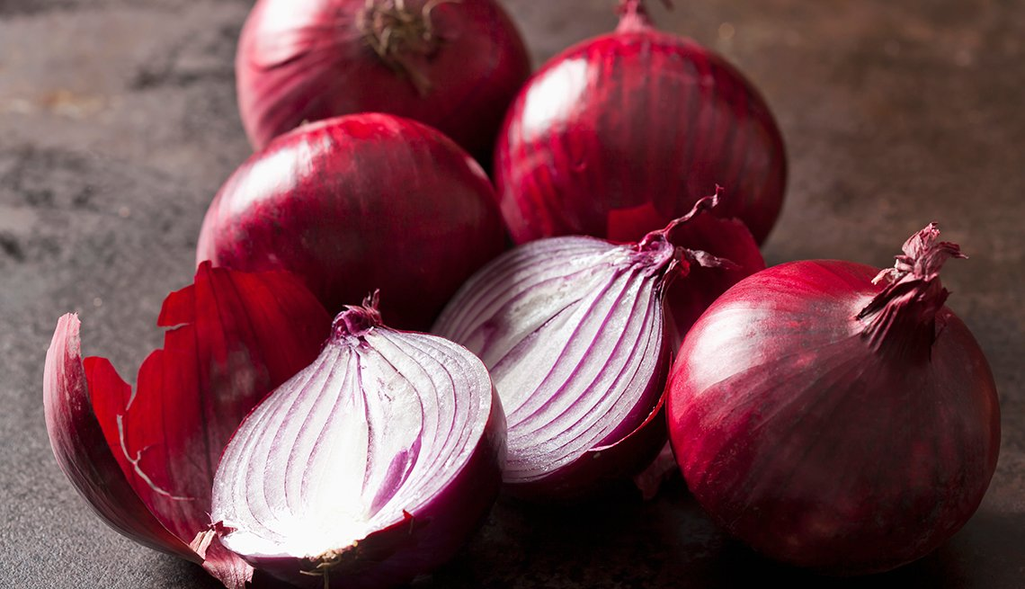 Close up of whole and sliced red onions.