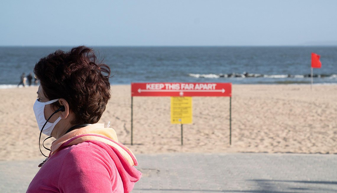 Woman walking next to the beach wearing a face mask, a sign encouraging social distancing is in the background.