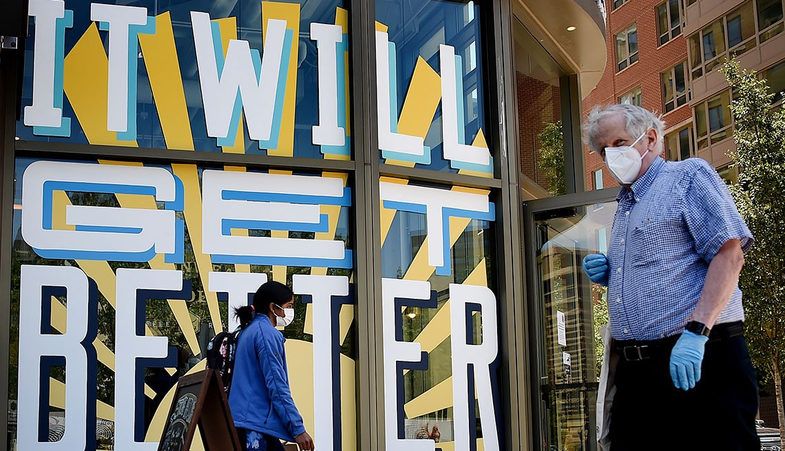 Man and woman in Arlington, Virginia walk past a mural that says It Will Get Better while wearing a mask.