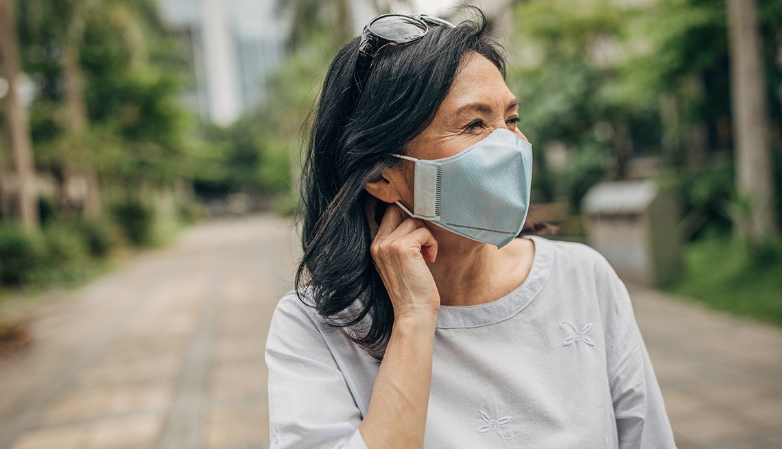 Una mujer usa mascarilla al aire libre