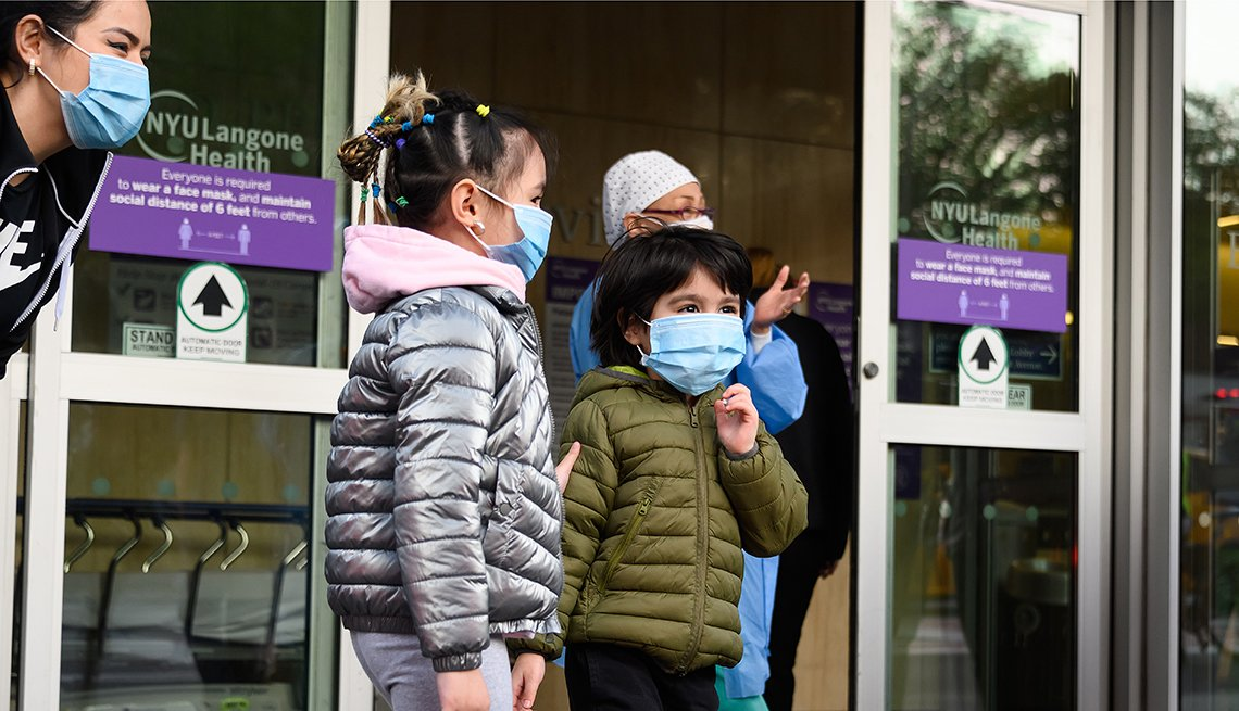 Two children stand outside hospital doors with hospital staff.