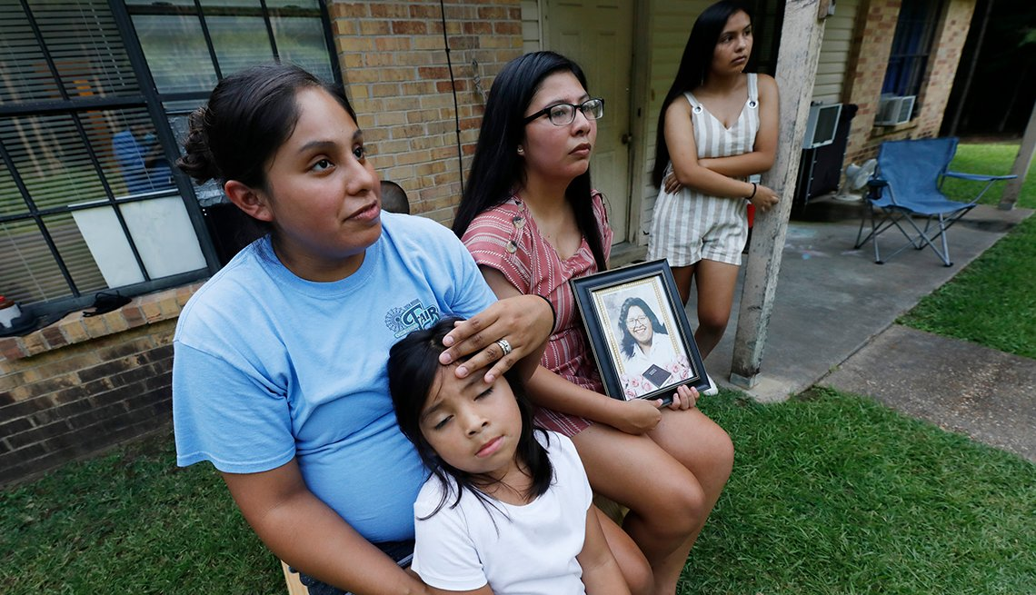 Sisters Kristi Wishork, left, consoles her daughter Renaya Farmer, 5, as she and her sisters Kristina Taylor, center and Kaydee Taylor, right recall the family pride and love their late mother, Sharon Taylor, had for their family, Tuesday, July 21, 2020 o