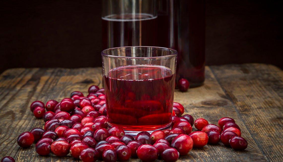 Un vaso con jugo de arándanos y arándanos frescos sobre una mesa