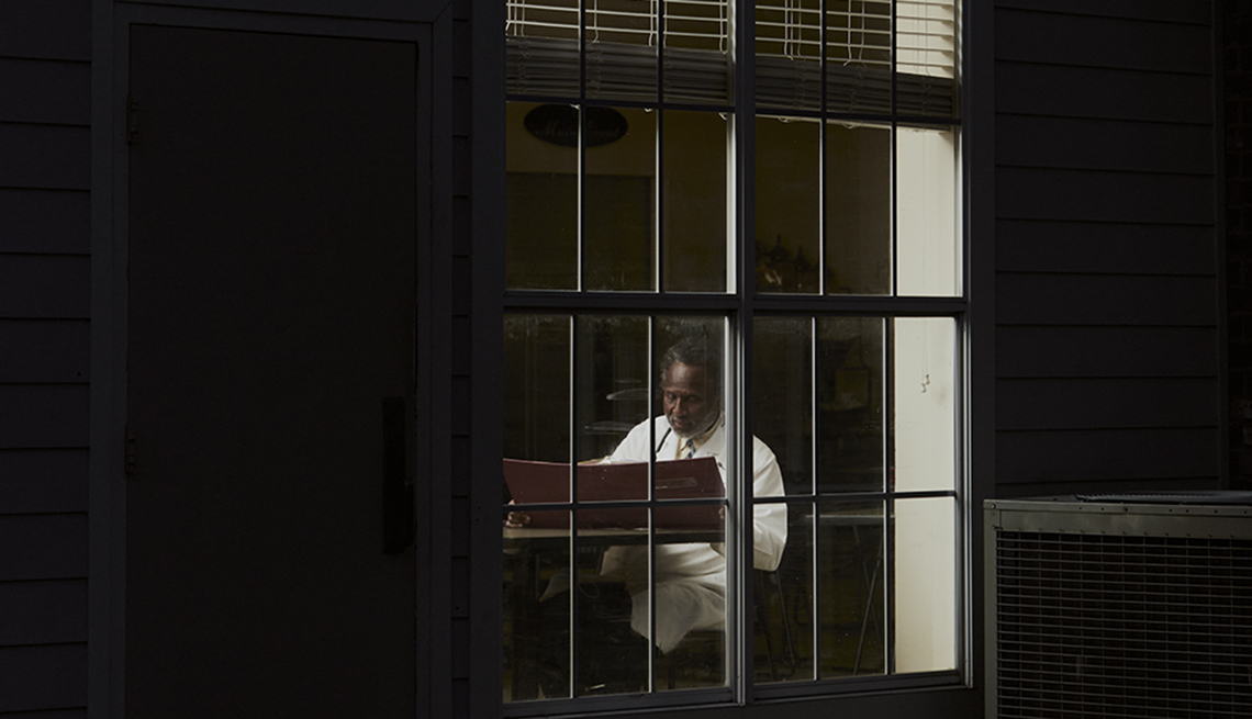 dr batie working into the night as seen from outside a window