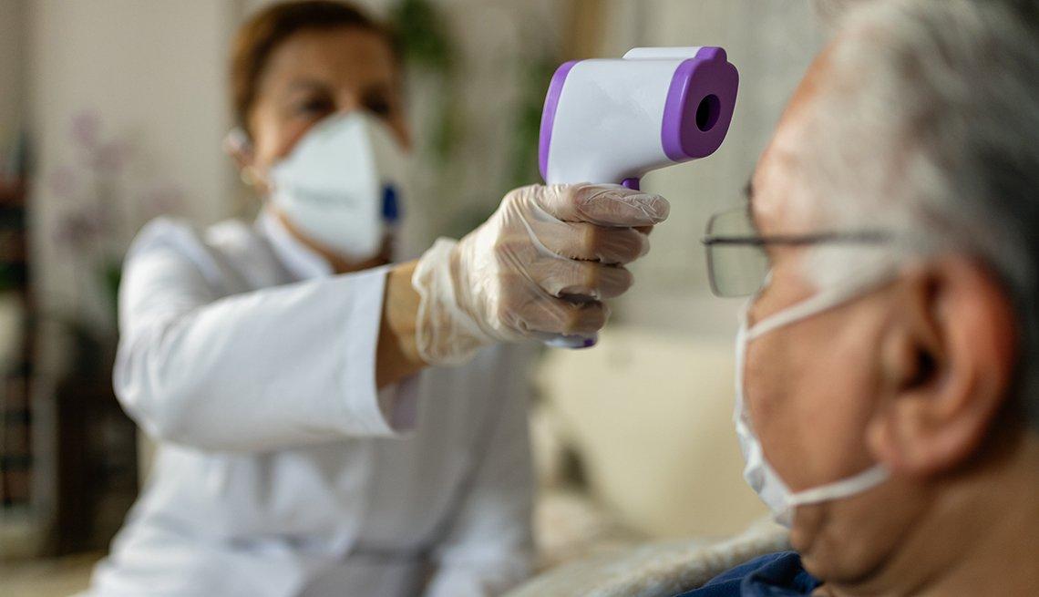Un médico le toma la temperatura a un paciente