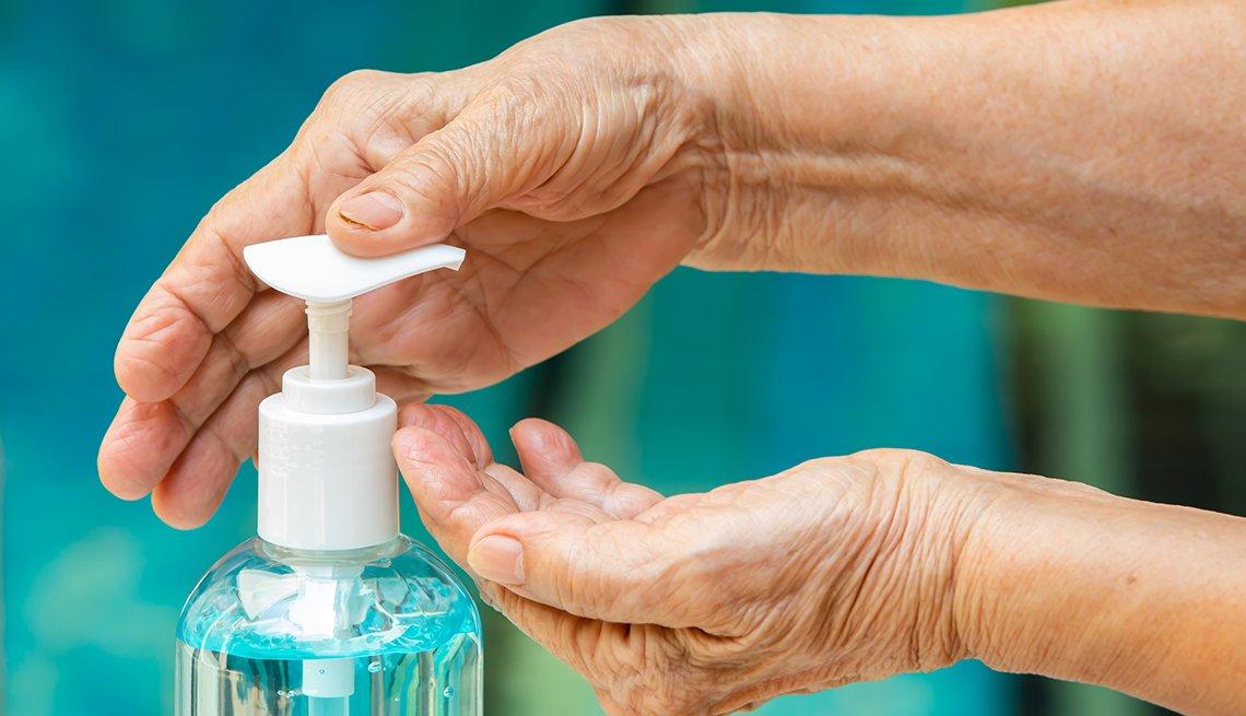 Una mujer se pone jabón desinfectante en sus manos