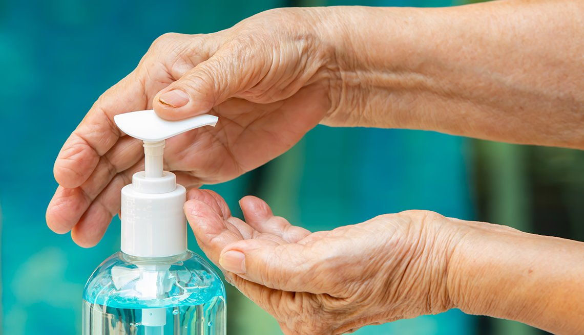 bottle of hand sanitizer showing a womans hands using it by depressing the pump top