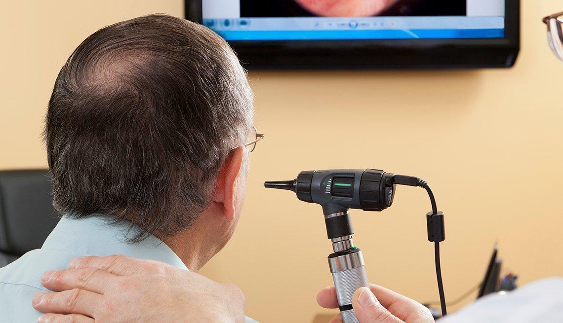 Doctor giving a man an ear exam
