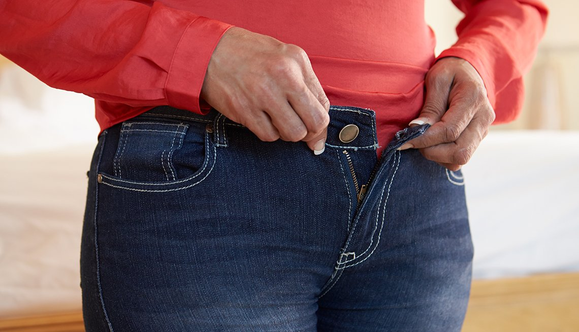 Woman buttoning her jeans.